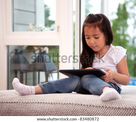Portrait of a young child in a home interior engrossed in a game on a digital tablet - stock photo