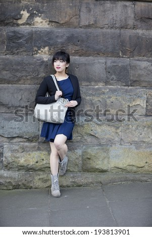 Portrait of a young Chinese woman leaning against a stone wall. Lifestyle image. - stock photo