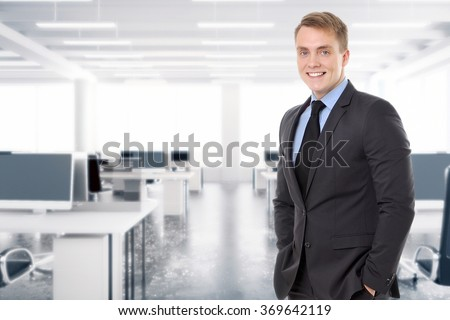 Portrait of a young, confident and attractive businessman in modern office. - stock photo
