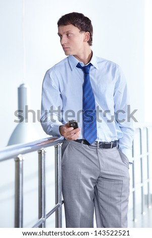 Portrait of a young confident businessman with cellular phone