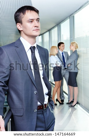 Portrait of a young confident businessman with working team on background
