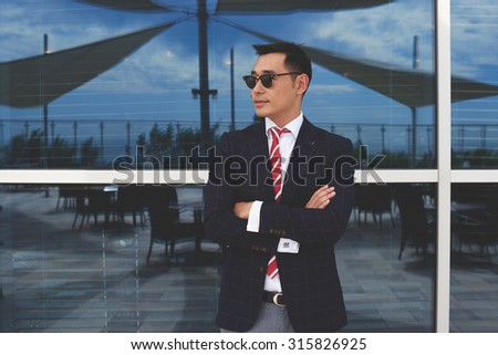 Portrait of a young confident managing director with arms crossed standing near modern office building, stylish intelligent asian men in sunglasses standing against glassy window with city reflection - stock photo