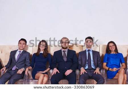 Portrait of a young confident workers dressed in corporate clothes sitting in hall before conference, International group of successful entrepreneurs in formal wear waiting for start business meeting  - stock photo