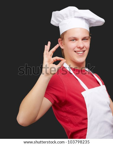 portrait of a young cook man doing a success symbol over a black background - stock photo