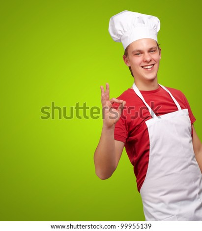 portrait of a young cook man doing a success symbol over a green background