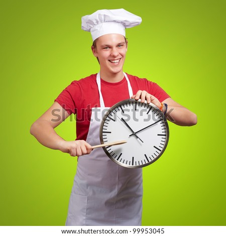 portrait of a young cook man pointing at a clock over a green background