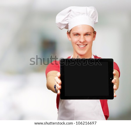 portrait of a young cook man showing a digital tablet indoor