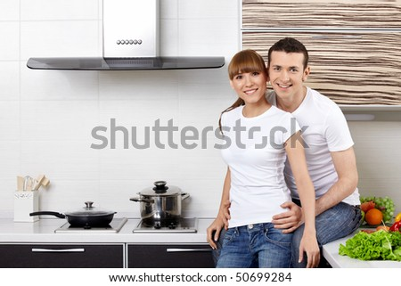 Portrait of a young couple at kitchen - stock photo