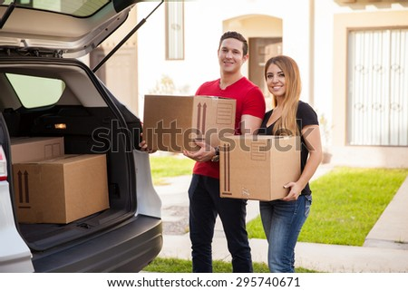 Portrait of a young couple carrying some boxes out of their car and moving into their new home - stock photo