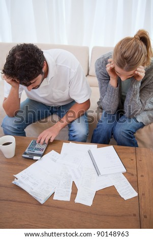 Portrait of a young couple doing their accounting in their living room - stock photo
