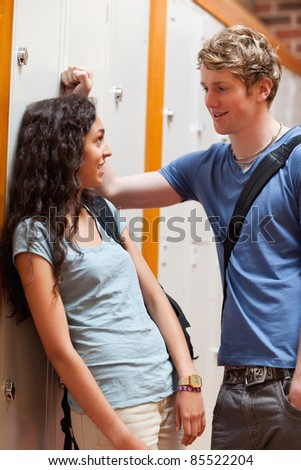 Portrait of a young couple flirting in a corridor - stock photo
