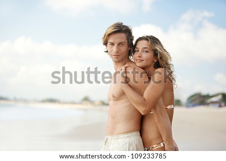 Portrait of a young couple hugging and being playful while standing on a beach on vacation. - stock photo