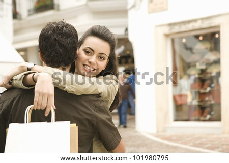 Portrait of a young couple hugging while shopping on vacation.