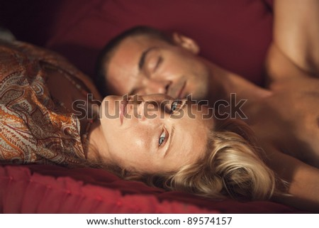 Portrait of a young couple laying down on a sofa. - stock photo