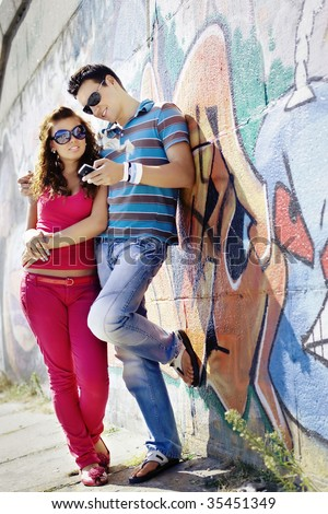 Portrait of a young couple looking at mobile phone - stock photo
