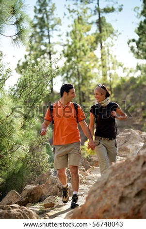Portrait of a young couple of hikers smiling - stock photo