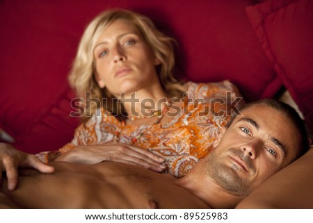 Portrait of a young couple relaxing on a sofa. - stock photo