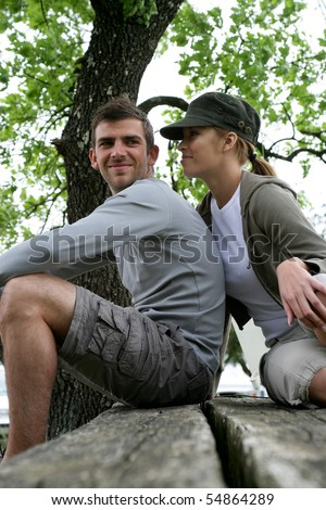 Portrait of a young couple sitting on a table - stock photo
