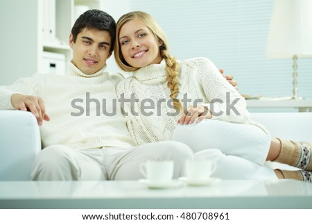 Portrait of a young couple sitting on sofa and looking at camera