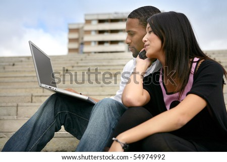 Portrait of a young couple sitting on steps with a laptop computer and a phone - stock photo