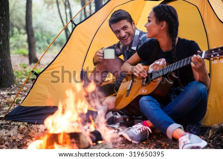 Portrait of a young couple sitting with guitar near bonfire in the forest - stock photo