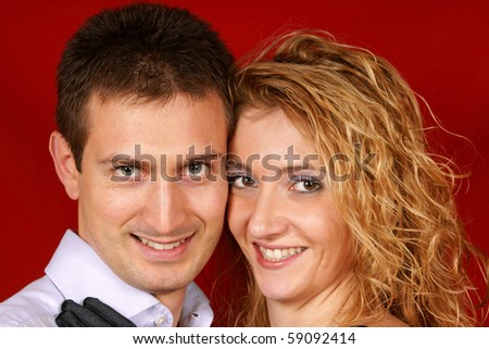Portrait of a young couple smiling at camera over a red background.