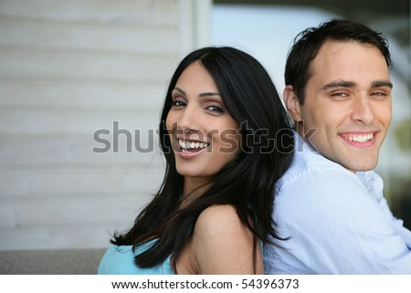 Portrait of a young couple smiling back to back - stock photo