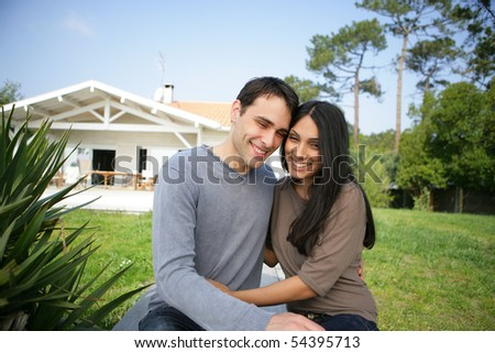 Portrait of a young couple smiling in front of a house - stock photo