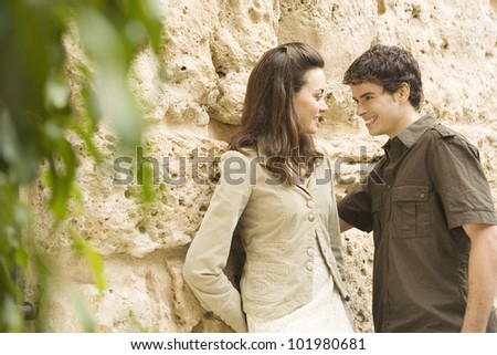 Portrait of a young couple smiling while leaning on an old textured wall. - stock photo