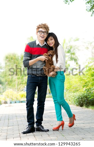 Portrait of a young couple with a dog in hands - stock photo
