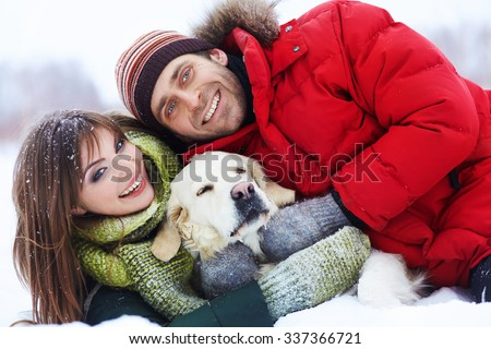portrait of a young couple with a dog on a winter walk. man and woman with labrador outdoors - stock photo