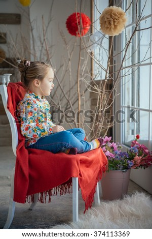 Portrait of a young cute kid on a chair near big window in a bright big white room  - stock photo