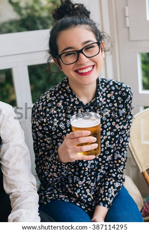 Portrait of a young cute modern woman drinking beer in a bar with friends - stock photo