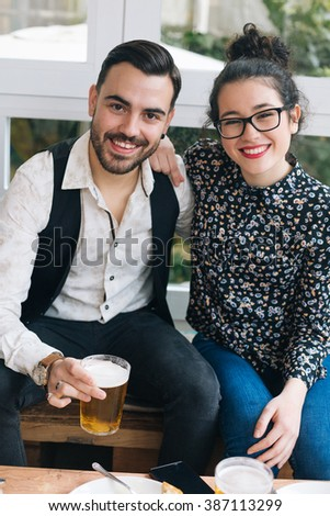 Portrait of a young cute stylish couple in a bar - stock photo