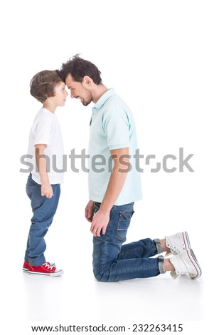 Portrait of a young dad kneeling and his son on a white background. - stock photo