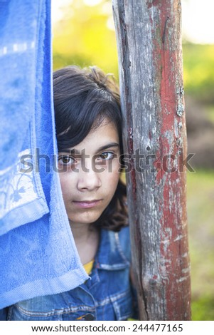 Portrait of a young dark-haired girl with expressive eyes in the village outdoors. - stock photo