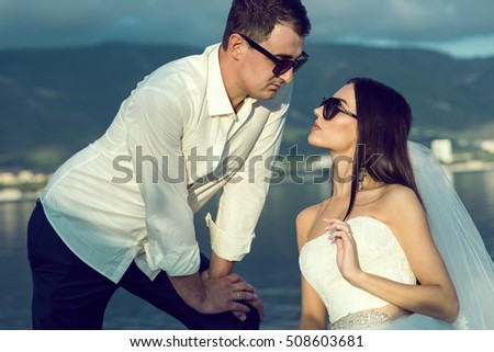 Portrait of a young dark-haired just married couple in stylish sunglasses and wedding gowns leaning to each other wishing to kiss. Wedding and eyewear concept. Close up. Outdoor shot