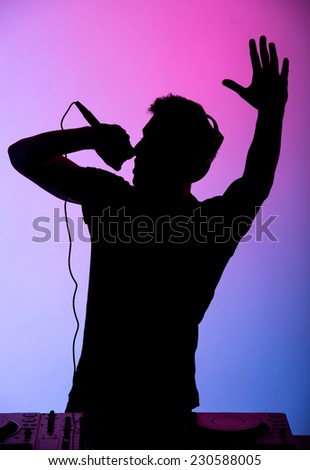 Portrait of a young DJ at work with a microphone on the colored background.
