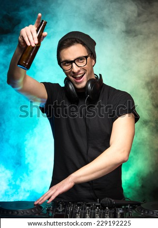 Portrait of a young dj with mixer, on foggy background. - stock photo