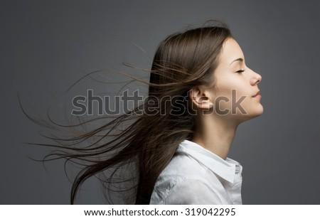 Portrait of a young dreamy brunette beauty with windswept hair. - stock photo