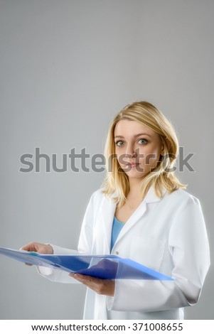 Portrait of a young energetic female scientist, tech or medical student with notes in blue folder on gray background. Space for your text.  - stock photo