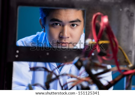Portrait of a young engineer looking at camera through the electronics - stock photo