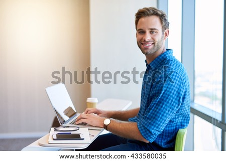 Portrait of a young entrepreneur in his new office, working at his laptop to create his new startup business - stock photo