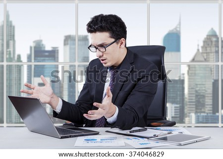 Portrait of a young entrepreneur looks confused and disappointed while looking at the laptop screen in the office