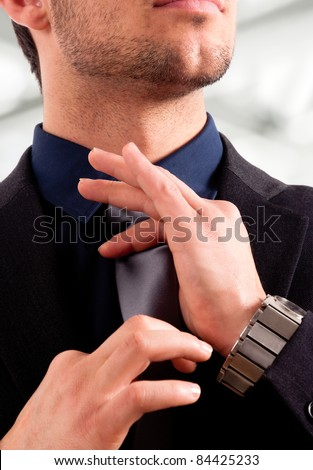Portrait of a young executive adjusting his tie - stock photo