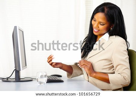 Portrait of a young executive female at work while show a white card - stock photo