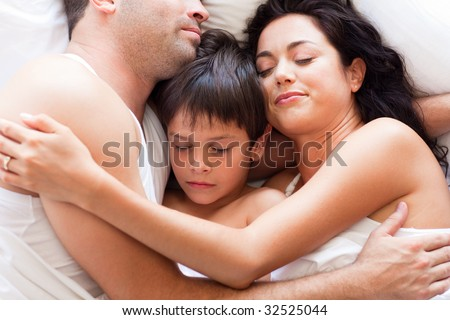 Portrait of a young family sleeping in bed