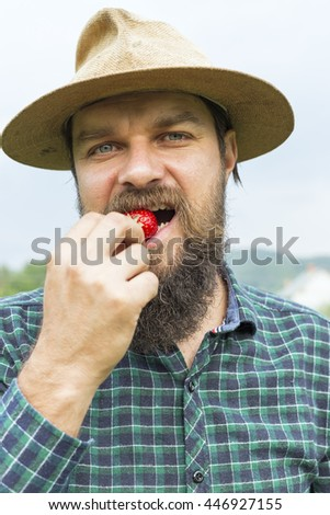Portrait of a young farmer  tasting a red fresh picked strawberry outside - stock photo