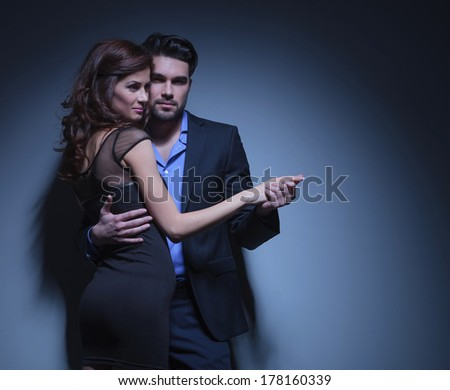 portrait of a young fashion couple dancing while the man is looking into the camera and the woman smiles away. on a dark blue background