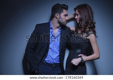 portrait of a young fashion couple looking at each other while the man holds a hand in his pocket and the other on the woman's back. on a dark blue background - stock photo
